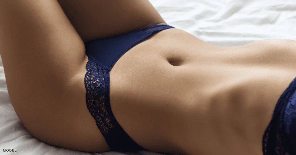 Woman with a flat stomach is happy with her tummy tuck results.