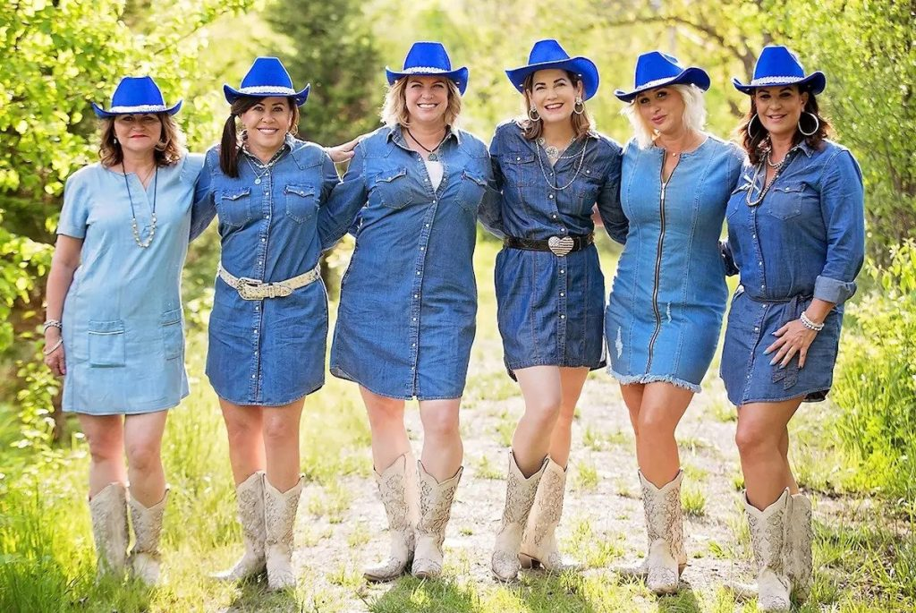 Aesthetica Surgery & Spa Staff Group Photo of Everyone Wearing a Blue Hat, Denim Dress, and White Boots.